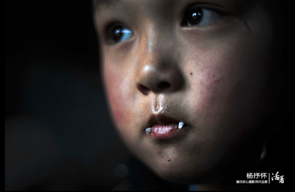 Grains of rice hang on the lips of a child benefitting from the free lunch program, an effort organized by journalists and promoted using Sina Weibo. Image via qq.com.