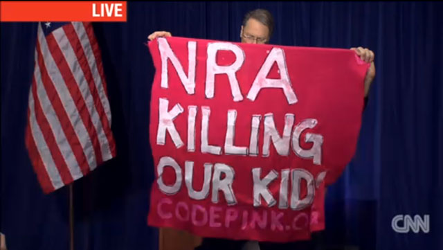 A sign held up by a Code Pink protester at the NRA's press conference on Friday, December 21 in Washington, DC. (via