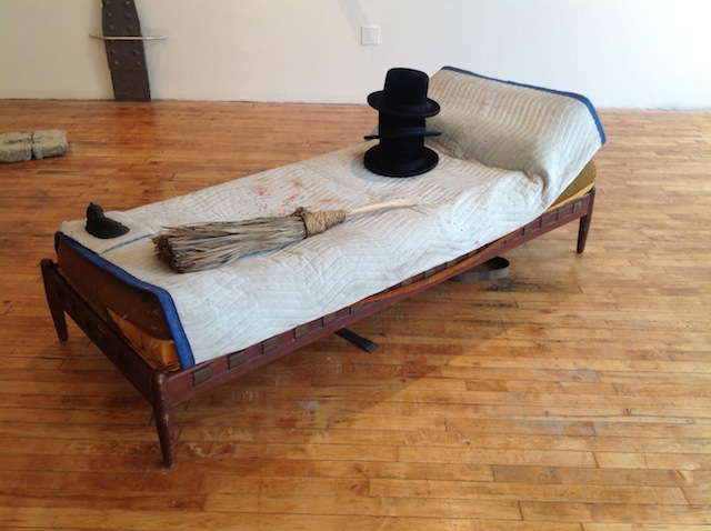 "Matt Freedman, ""Hats and Broom on Bed with Drinking glass Reflecting Full Moon"" (2013). Epoxy  plastic, found objects, 36 x 72 x 18 inches."