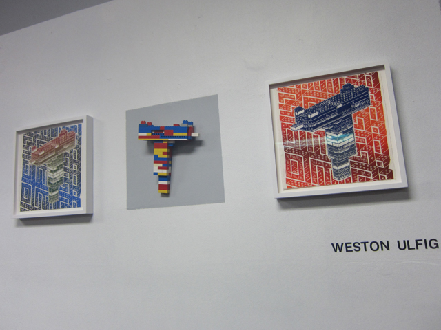 "Prints and a lego gun by Weston Ulfig, also part of the ""Magic Kingdom"" exhibition"