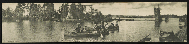 Panorama of the Hiawatha play, Ya-Way-Ga-Mug, Petoskey, Michigan, Photograph by Alton G. Cook (1906), showing three canoes being paddled by American Indians, on the far shore is a village of tepees, on the near shore are canoes pulled onto a pier.