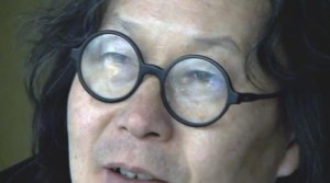 "Xu Bing, in his signature ""owl"" glasses, still from ""Phoenix,"" Itinerant Pictures (c. 2013)"