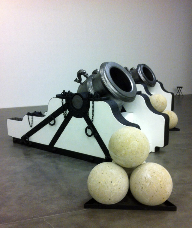 """Chris Burden, """"Pair of Namur Mortars"""" (2013). Bronze, wood, iron, steel, stone. Dimensions: Each mortar: 60 × 132 × 48 inches. Each stack four cannon balls: 36 × 36 inches. Approximate weight of each mortar, cradle, and four cannonballs: 12,000 lbs. Courtesy the artist and Gagosian Gallery."""