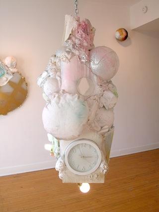 "Sabina Ott, ""why is a pale white not paler than blue,"" (2012), polystyrene, canvas, burlap, acrylic, spray enamel, mirror, clock, spray foam, light fixture, metal chain, 100″ x 24″ x 24″ (courtesy Riverside Arts Center) (click to enlarge)"