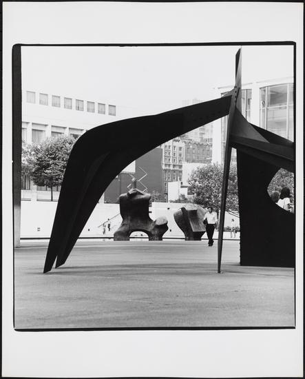 "Edmund V. Gillon, [""Le Guichet"" (""The Box Office"") stabile, ""Reclining Figure"" in the background.] (c. 1976), gelatin silver print, 10 x 8 in"