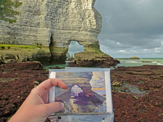 """A researcher on the Texas State team holds a postcard of Monet's """"La Porte d'Amont, Étretat"""" (c. 1868–69) in front of the present-day scene (via txstate.edu) (click to enlarge)"""