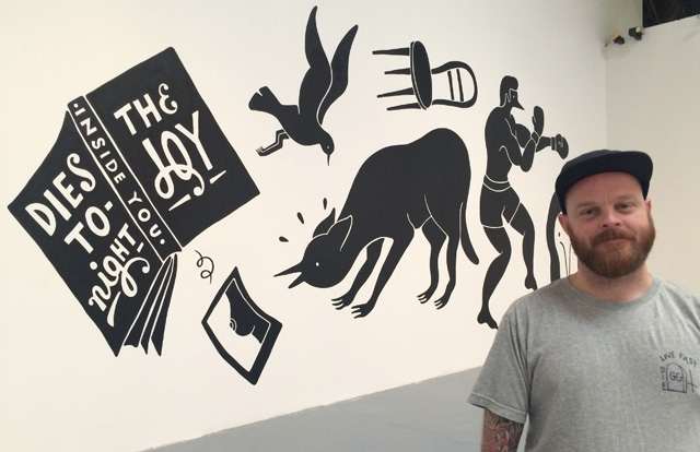Curator Shannon Michael Cane with Farra's mural inside MOCA's Geffen Center, where the LAABF is taking place.