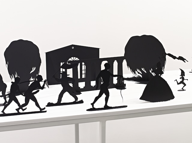 "Kara Walker, ""Burning African Village Play Set with Big House and Lynching,"" (2006). Painted laser-cut steel, sizes vary; table dims: 38 1/4 x 90 x 24."""