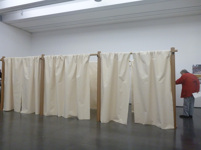 A visitor checks out Ban's Paper Partition System, set up after the Great Japan Earthquake and the 2011 tsunami.