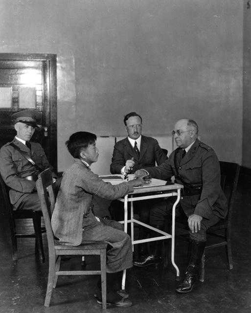 A Chinese immigrant is interrogated by US immigration inspectors on Angel Island, 1923. National Archives, College Park, MD (90-G-124-479).