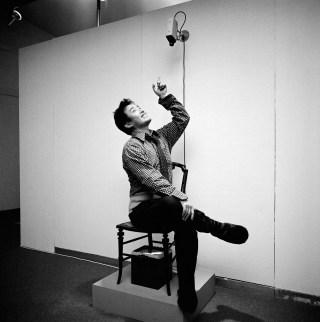 "Nam June Paik sitting in ""TV Chair"" (1968/1976) in 'Nam June Paik Werke, 1946–1976: Music, Fluxus, Video,' 1976 (photo © Friedrich Rosenstiel, Cologne) (click to enlarge)"