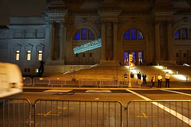"The Illuminator projects ""Koch = Climate Chaos"" on the facade of the Metropolitan Museum of Art on Tuesday, September 9, 2014. (image via Occupy Museums)"
