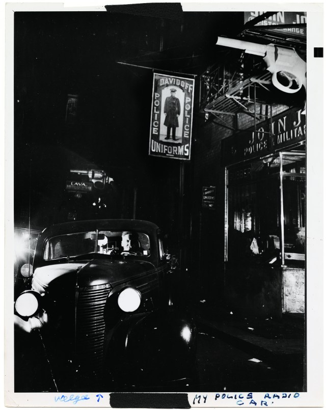 Weegee in his car in front of the police supply shops at 5 & 6 Centre Market Place (1942). The photographer's studio was above one of the stores. (all photographs courtesy Prestel)