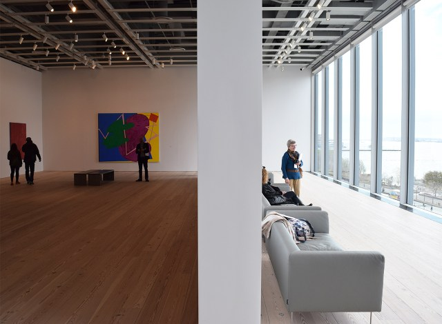 On the fifth floor, couches face a wall of glass that looks out onto the Hudson, allowing some natural light to filter through to the adjacent galleries