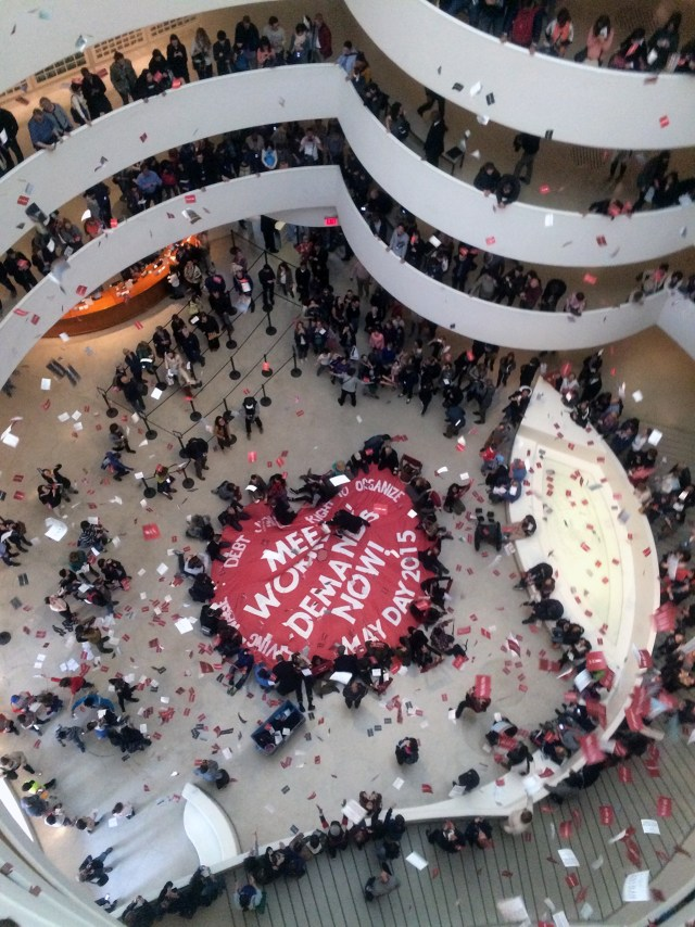 """Members of the Gulf Ultra Luxury Faction (known as G.U.L.F.) unveiled a large parachute in the Guggenheim Museum rotunda with the words """"Meet Workers Demands Now"""" on May Day. (photo by Benjamin Sutton for Hyperallergic)"""
