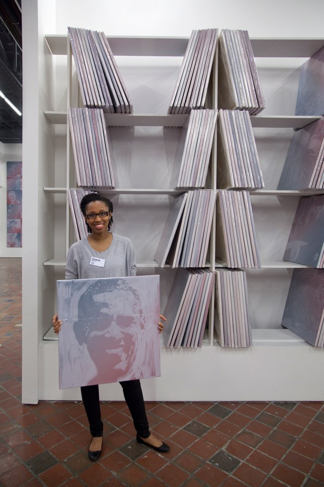 MOCAD intern Juana Williams handles an individual painting from the collection wall.