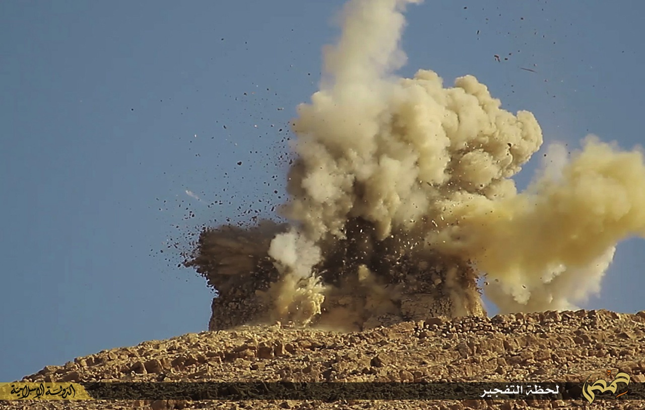 A photo republished by the AP shows ISIS destroying a tomb at the ancient site of Palmyra.