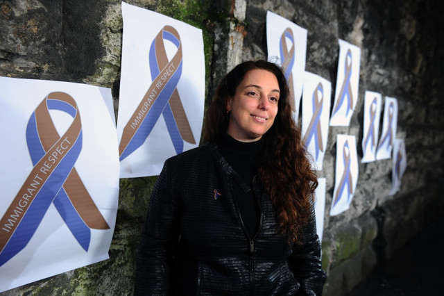 Tania Bruguera stands in front of posters for her Artes Mundi exhibition inside the National Museum in Cardiff (photo by Tom Martin ©WALES NEWS SERVICE)