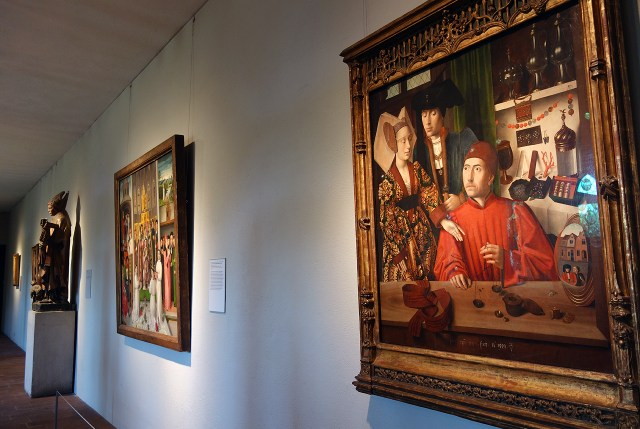 """Installation view of 'Treasures and Talismans: Rings from the Griffin Collection,' with at right: Petrus Christus, """"A Goldsmith in his Shop"""" (Netherlandish, 1449), oil on oak panel"""