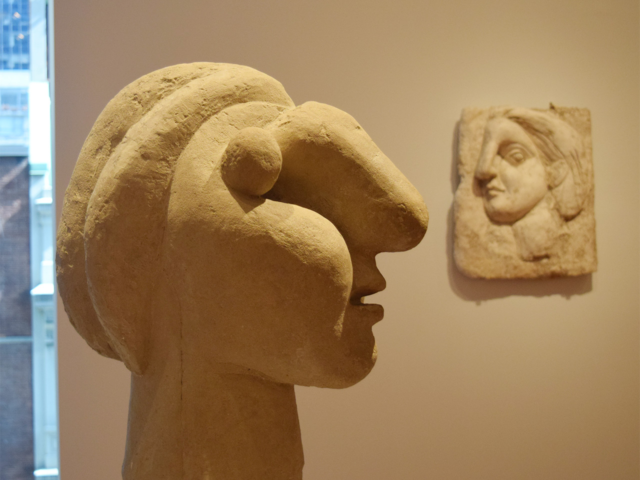 "Installation view of 'Picasso Sculpture' at the Museum of Modern Art with Pablo Picasso's ""Head of a Woman"" (1931, cement) at left and ""Head of a Woman"" (1931, plaster) at right"
