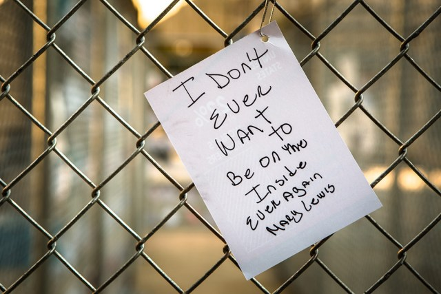 "A paper affixed to the chain-link fence of ""Labyrinth"" (2015)"