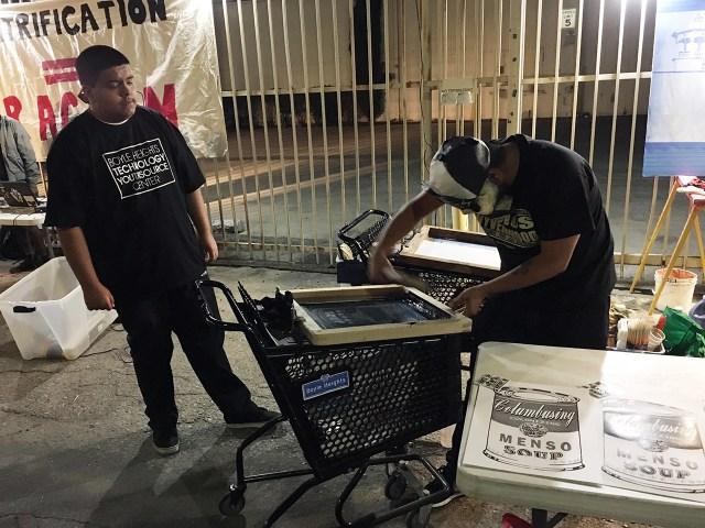 Artist Nico Avina (right) screenprinting at 'Ambularte' mobile art exhibit in Boyle Heights, Los Angeles
