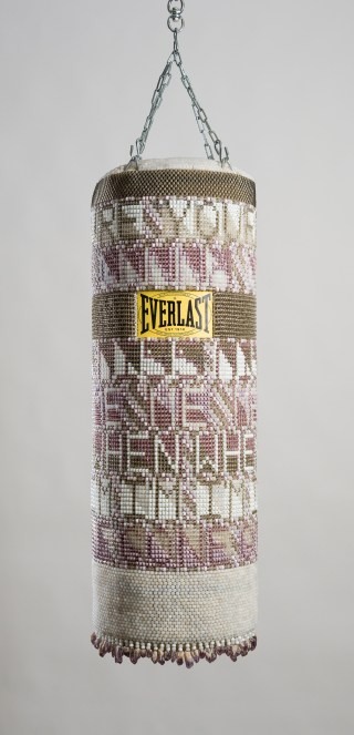 "Jeffrey Gibson, ""YOU'RE GONNA MISS ME WHEN I'M GONE"" (2015), repurposed punching bag, glass beads, artificial sinew, amethyst, steel, 41 x 14 x 14 inches"