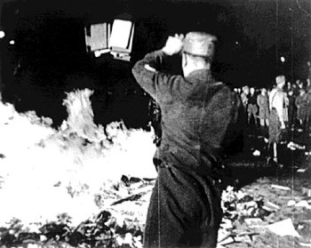 """On May 10, 1933, Nazis in Berlin burned works by leftists and other authors considered """"un-German"""", including thousands of books looted from the library of Hirschfeld's Institut für Sexualwissenschaft. (in the collection of the US National Archives, via Wikipedia)"""