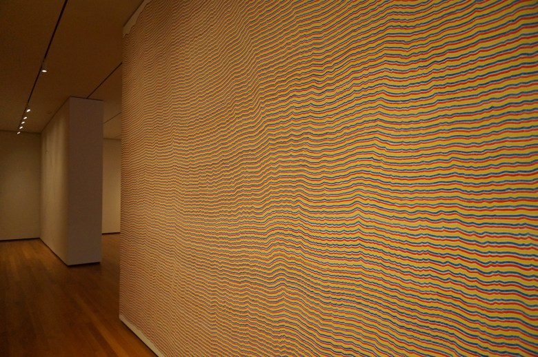 """Sol LeWitt, """"Wall Drawing #797: The first drafter has a black marker and makes an irregular horizontal line near the top of the wall. Then the second drafter tries to copy it (without touching it) using a red marker. The third drafter does the same, using a yellow marker. The fourth drafter does the same using a blue marker. Then the second drafter followed by the third and fourth copies the last line drawn until the bottom of the wall is reached"""" (1995), black, red, yellow, blue marker on wall"""