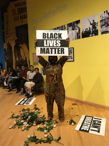 """Black Lives Matter co-founder Patrisse Khan-Cullors holds a protest sign during her performance """"Remembering '92."""""""