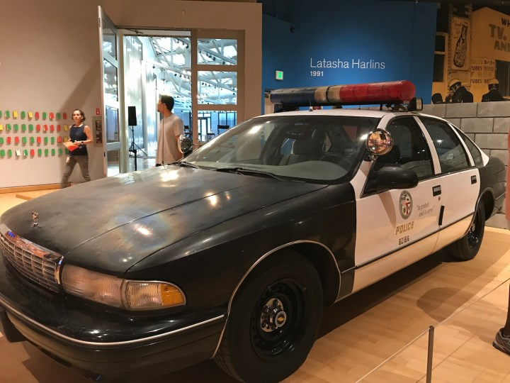 A 1990s police car ominously sits in the back of the exhibition space in No Justice, No Peace: LA 1992 at the California African American Museum.
