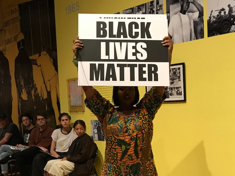 "Black Lives Matter co-founder Patrisse Khan-Cullors holds a protest sign during her performance ""Remembering '92."""