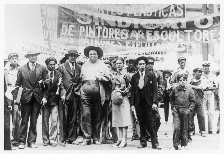 "Tina Modotti, ""Diego Rivera and Frida Kahlo with Members of the Artists' Union on the May Day March"" (1929) (courtesy La Fábrica)"