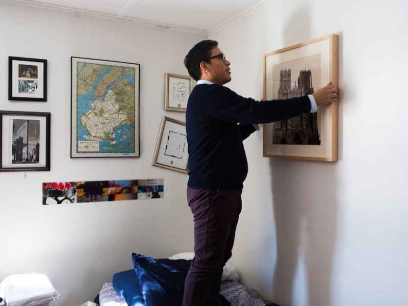 A Williams College student hanging a work on loan from the WALLS program in his dorm room (photo by Julia Sabot, courtesy Williams College Museum of Art)