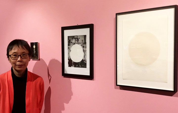 Curator Reiko Tomii with works by Yutaka Matsuzawa featuring the white circles the artist regarded as visual aids for meditation; he intentionally displayed the white-ink-on-paper silkscreen on the right with its back side facing out (photo by the author for Hyperallergic)
