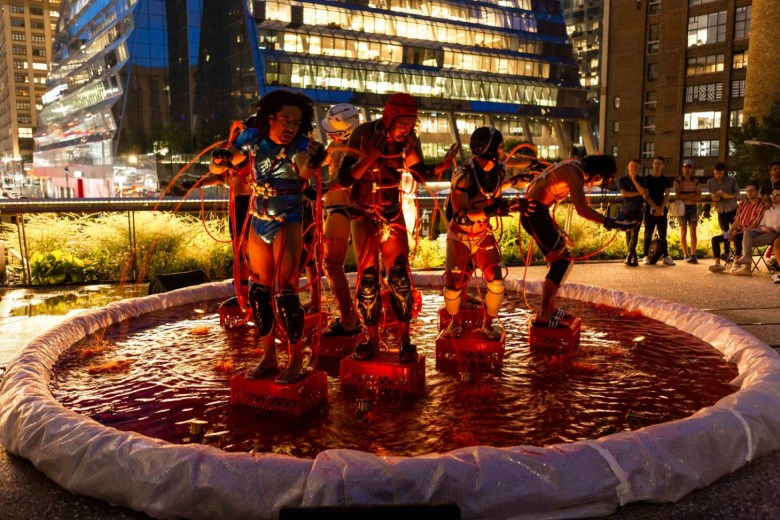 5 performers stand in various postures inside a small pool of water on the high line plinth