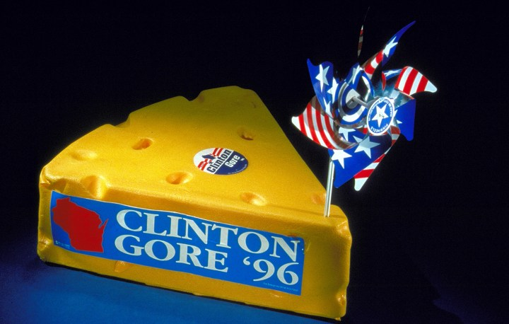 "Shaped like a block of swiss cheese, this delegate hat from the 1996 Democratic National Convention is decorated with a ""Clinton Gore '96"" sticker and other stars and stripes decoration."
