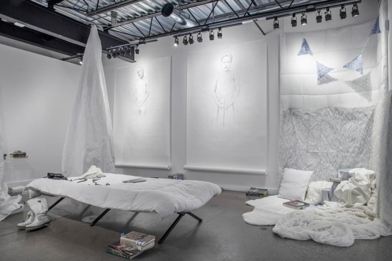 View onto a white-walled gallery space with concrete flooring. Below a bar of track lighting, hang two large-scale, seemingly unfinished drawings of figures. Next to the two paper works is a white comforter, which touches down to the floor and is augmented by white pillows and white bed sheets. At the foreground, a cot with white bedding stands, with a pair of white boots. Scattered throughout the space are small stacks of books.