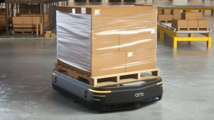 Image is of a OTTO industrial robot carrying a large load of boxes in a warehouse environment.