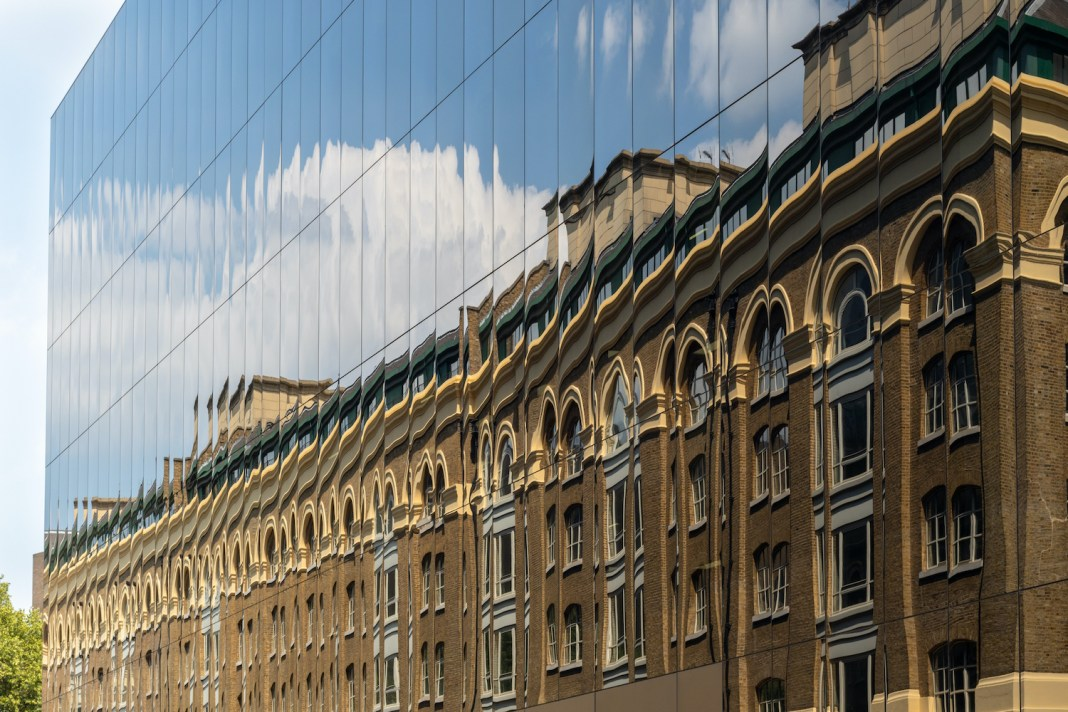 New versus old - an old brick building reflected in windows of modern new facade