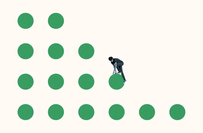 Full length of young courageous man climbing on green circles against white background
