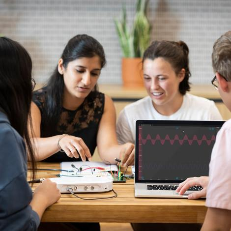 Students at a table use a Moku Go device to test a circuit board.