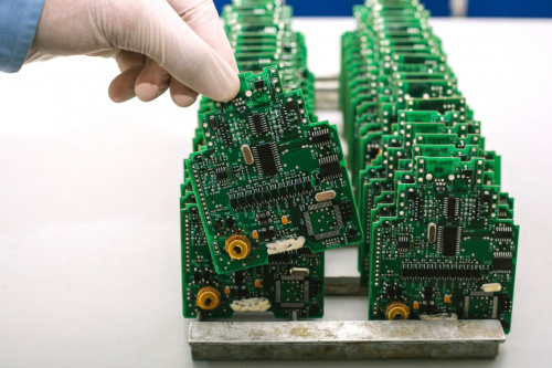 Two rows of green PCBs about to be tested
