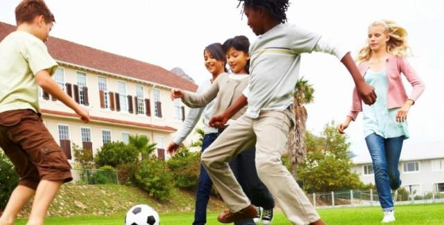 Energetic school children playing football, outdoors