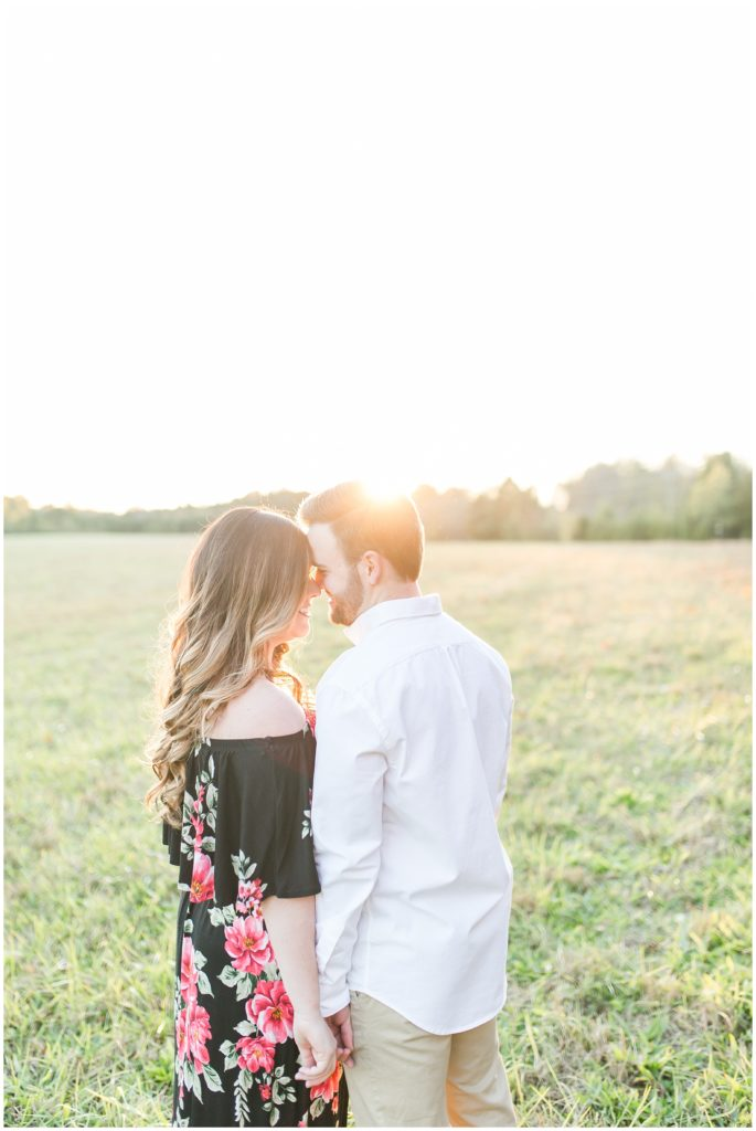 engagement session in a field at sunset golden hour