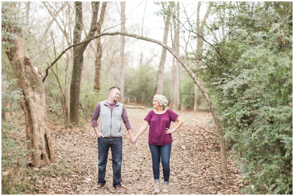 engaged couple posing in the woods