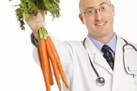 Caucasian mid adult male physician holding bunch of carrots.