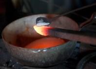 For å ikkje få for mykje glødeskal på jernet strør Mattias på boraks som eit flussmiddel. Når dette smeltar vert det liggande som ei beskyttande hinne utanpå jarnet. Foto: Roald Renmælmo