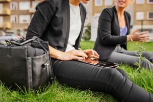 Two women sitting in grass and using digital tablet