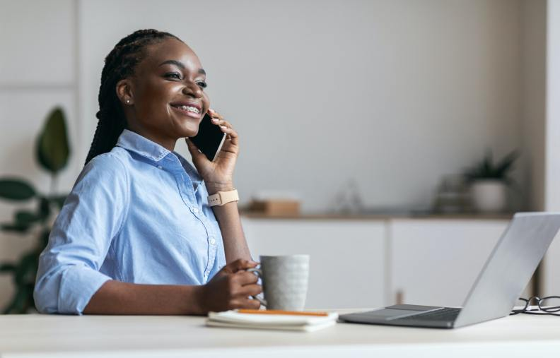 Relax At Work. Happy Black Secretary Talking On Cellphone And Drinking Coffee